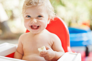 Laughing toddler eating in high chair